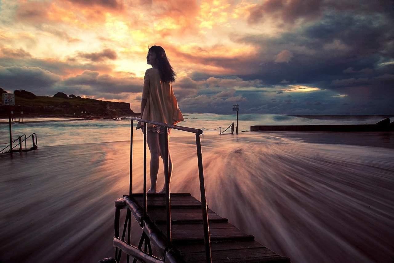 אישה בשקיעה בחוף הים